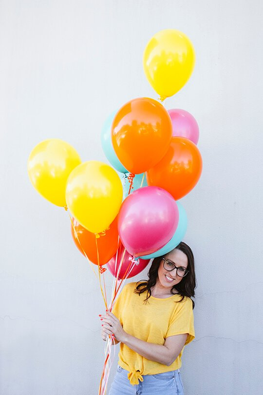 Graphic Designer holding colourful balloons