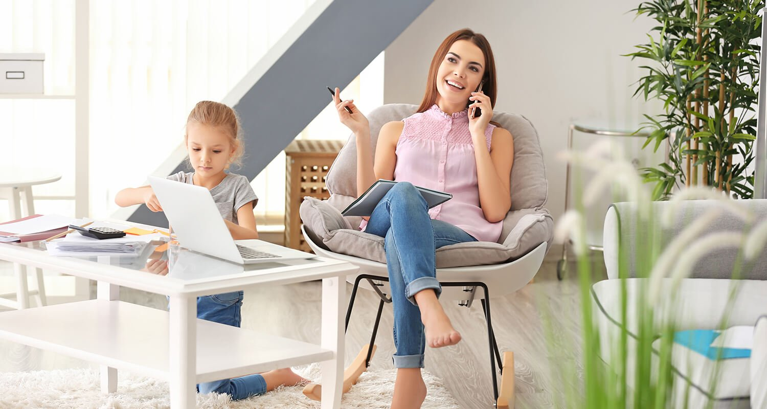 working mum on the phone while her daughter plays happily