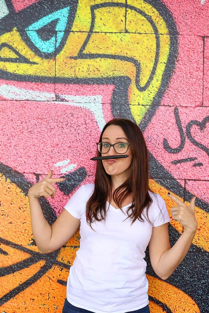 Brisbane based brand designer Kat Potter standing against a colorful graffiti wall