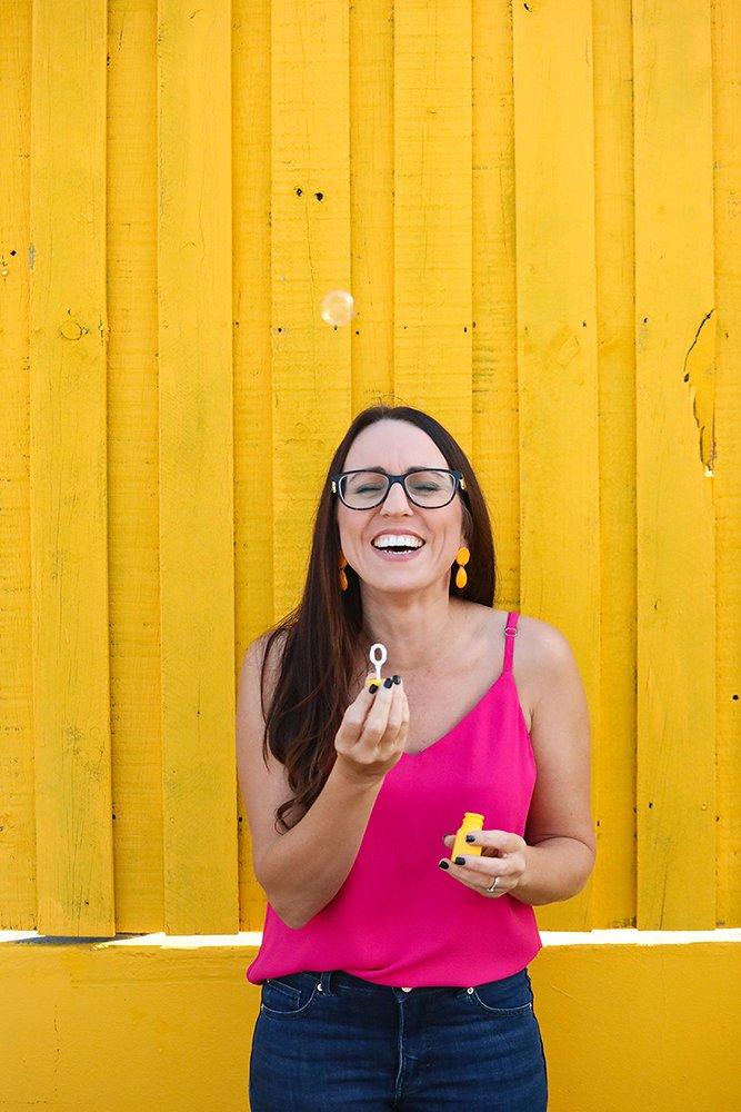 happy Brisbane graphic designer against yellow wall