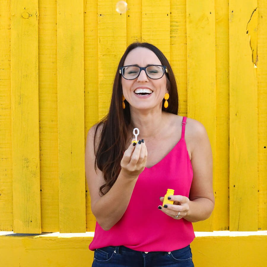 Kat Potter Blowing bubbles in front of a yellow wall
