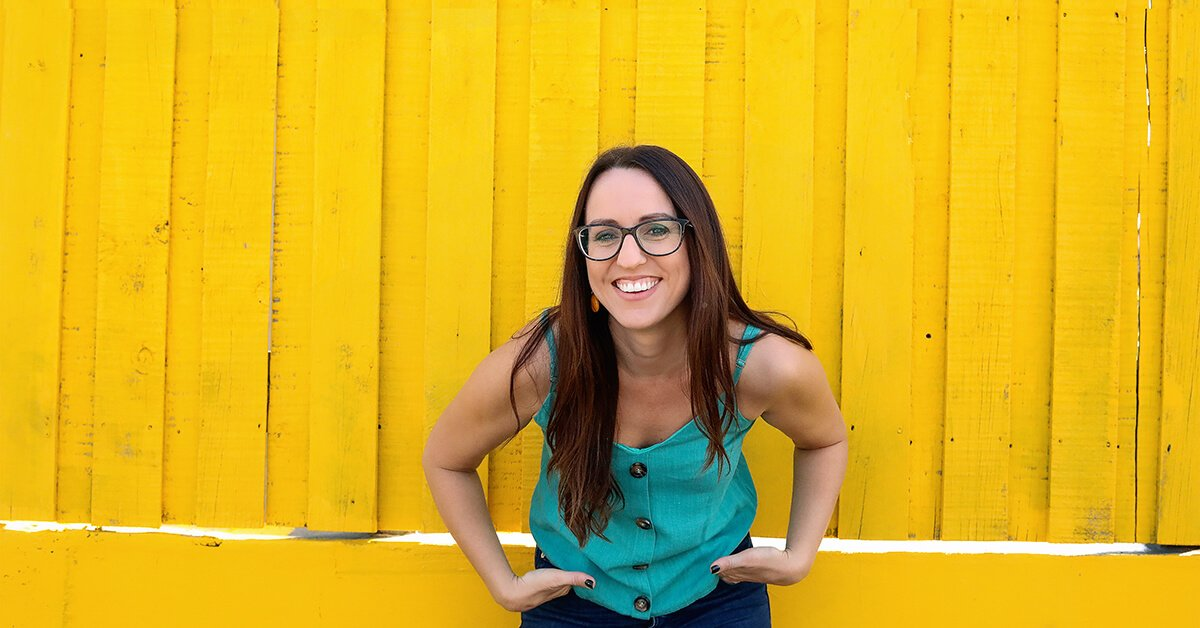 Kat Potter standing against a yellow wall